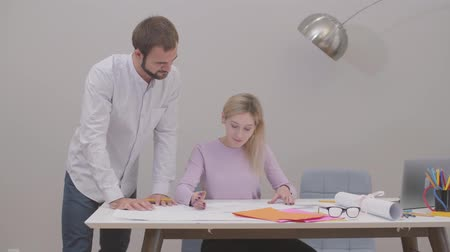 implementation : Bearded Caucasian man standing next to the table and looking at his assistants drawings. Young female designer implementing her idea into life. Professionals discussing project at the office. Stock Footage
