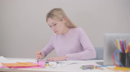 redaccion : Portrair of young blond Caucasian woman sitting at the office and drawing blueprints. Her male colleague coming up with drafts. Professionals discussing ideas at workplace.