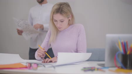seçkin : Portrait of beautiful blond Caucasian woman drawing blueprints at the office. Her male colleague standing at the background with drafts. Professional architect showing his works to coworker.