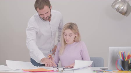 implementation : Caucasian man and woman discussing their project in the office. Young professional architects improving draft, female designer drawing blueprints. Professionals at workplace. Stock Footage