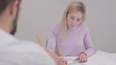 seçkin : Close-up portrait of blond Caucasian woman drawing blueprint, shaking customers hand and smiling. Professional designer working in the office. Specialist implementing ideas on paper. Stok Video