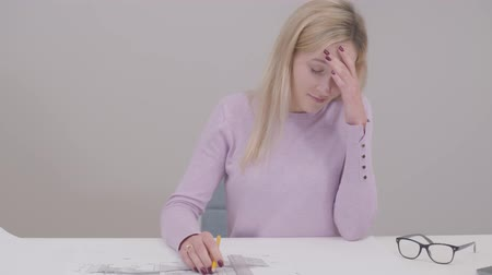 implementation : Portrait of concentrated Caucasian woman drawing blueprint, doing mistake and breaking pencil. Irritated female designer having problems with idea implementation. Professional at workplace.