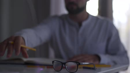 seçkin : Blurred Caucasian man working with papers at the background. Male professional architect doing project sitting at the table. Focused on elegant black eyeglasses lying on the foreground.