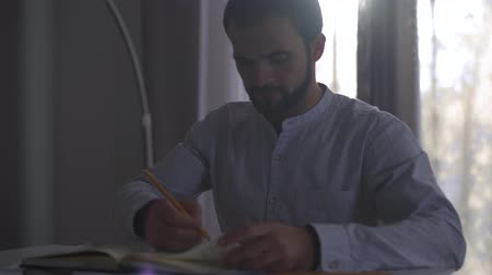 seçkin : Handsome Caucasian man sitting indoors in the evening sunlight and taking notes in notebook. Male professional architect doing project sitting at the table.