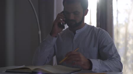 implementation : Young Caucasian man talking on smart phone in the evening sunlight and taking notes in notebook. Male professional architect doing project sitting at home or in the office.