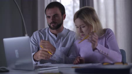 construtor : Confident adult Caucasian man reaching agreement with his pretty female coworker regarding their new project. Professional architects sitting at the table with drawings and looking at laptop screen. Stock Footage