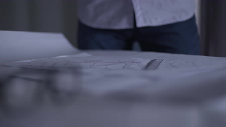 implementation : Close-up of architectural drawings lying on the table. Irritated man putting fists angrily upon them. Problems with design concept, implementation of project. Stock Footage