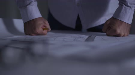 angrily : Close-up of male Caucasian fists putted angrily upon architectural drawings lying on table. Adult architect throwing out pencil dissatisfied with his work. Problems with the implementation of project.