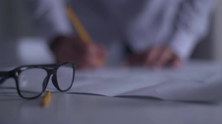 seçkin : Blurred male Caucasian hands drawing blueprint at the background. Adult architect or designer working on the new project. Focused on black eyeglasses lying on the table at the foreground.