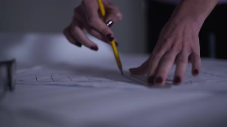 uygulanması : Close-up of female Caucasian hands with red manicure drawing blueprint and taking notes. Adult architect working on the new project. Professional in the process of her work. Stok Video