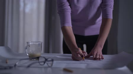 латте : Young female Caucasian architect drawing the blueprint and accidentally pouring her coffee on the project. Unlucky professional designer spoiling her work.
