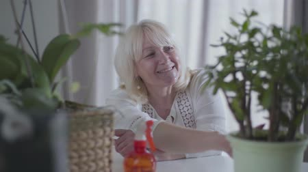 гордый : Portrait of happy Caucasian senior woman admiring her houseplants. Nice mature blond lady looking at her gardening and smiling. Hobby, pastime, leisure.
