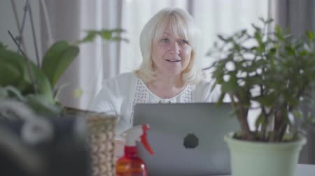 houseplant : Beautiful blond mature woman sitting with laptop at home behind her gardening. Portrait of Caucasian retiree sitting between green home plants in pots and using gadget. Hobby, pastime, leisure.