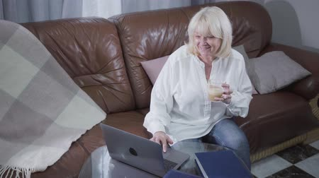 inspirar : Top view of attractive senior Caucasian woman watching pictures or photos on laptop screen and smiling. Blond mature retiree using laptop at home. Leisure activity, pastime.