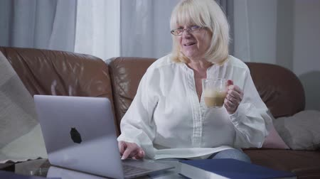 латте : Positive Caucasian senior woman in eyeglasses sitting at couch with coffee and surfing internet. Blond mature retiree using laptop at home. Leisure activity, pastime. Стоковые видеозаписи
