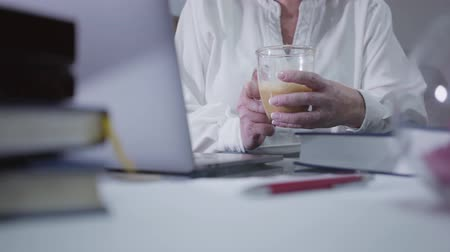 megjegyzés : Close-up of mature female hands holding coffee cup and using laptop. Senior Caucasian woman surfing internet at home. Hobby, pastime, leisure, social networks.