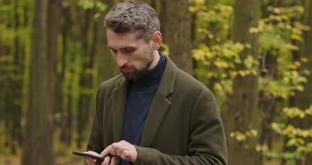 yaprak döken : Portrait of a handsome gray-haired Caucasian man in the forest with the smartphone, shaking his head and taking picture of surroundings. Cinema 4k footage ProRes HQ.