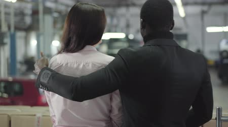 прокат : Back view of biracial couple choosing new car in showroom. Young African American man hugging beautiful Caucasian woman and smiling. Multiracial family purchasing car. Car dealership, car business.