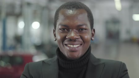 прокат : Close-up face of young African American car dealership manager looking at camera and smiling. Owner of automobile showroom standing on the background of new automobiles. Car dealership, car business. Стоковые видеозаписи