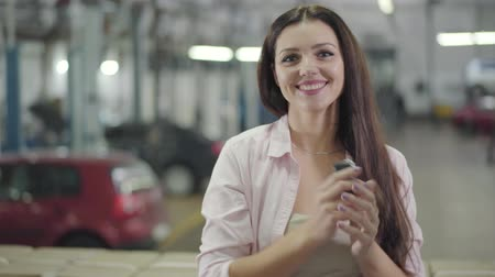 businesslady : Portrait of satisfied Caucasian woman showing car keys and smiling. Young beautiful girl purchasing new automobile in showroom. Happy client posing in car dealership. Car business, happy customer.