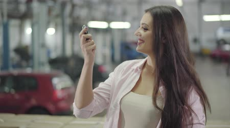 прокат : Happy young Caucasian girl kissing car keys, clapping hands and smiling. Beautiful woman buying new automobile in car showroom. Happy client posing in car dealership. Car business, happy customer. Стоковые видеозаписи