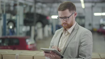 contratar : Young confident Caucasian salesman using tablet, looking at camera and gesturing yes by shaking head. Successful car dealer in eyeglasses and suit making deal online. Car dealership, car business.