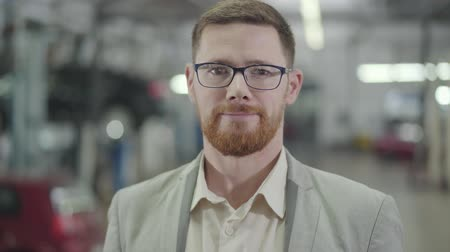 redhead suit : Close-up portrait of smart Caucasian man with red beard looking at camera and gesturing yes by shaking head. Adult male car dealer posing at the background of showroom. Car dealership, car business. Stock Footage
