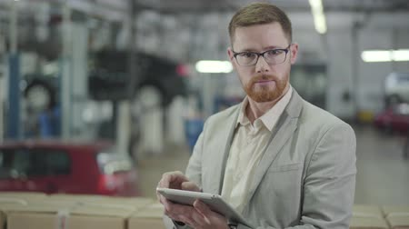 прокат : Portrait of redhead Caucasian man in eyeglasses making deal online using his tablet, looking at camera and gesturing yes by shaking head. Car dealership, car business. Стоковые видеозаписи