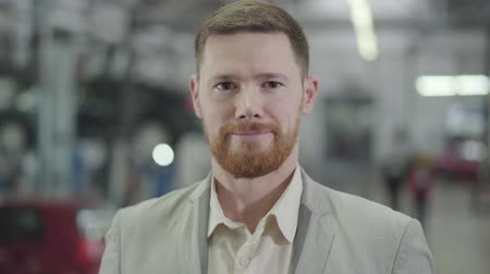прокат : Close-up face of adult Caucasian man with brown eyes and red beard gesturing yes by shaking head, and smiling. Male car dealer posing at the background of showroom. Car dealership, car business. Стоковые видеозаписи