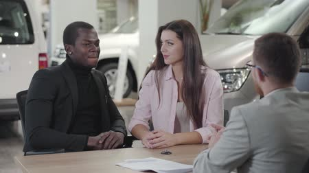прокат : Happy young multiracial couple sitting in car dealwership and talking with salesman. African American man and beautiful Caucasian woman buying new automobile. Car dealership, car business.