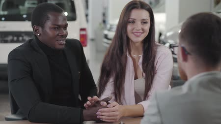 başarı : Handsome African American man holding girlfriends hand, talking to car dealer. Happy multiracial family buying new automobile. Biracial couple making deal in showroom. Car dealership, car business.