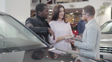 прокат : Excited Caucasian woman and positive African American man talking with car dealer about automobile specifications. Multiracial family buying new car in showroom. Car dealership, car business.