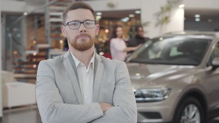 redhead suit : Portrait of successful Caucasian car dealer crossing arms and gesturing yes by shaking head. Salesman looking at camera and smiling. Multiracial couple admiring their new automobile at the background.