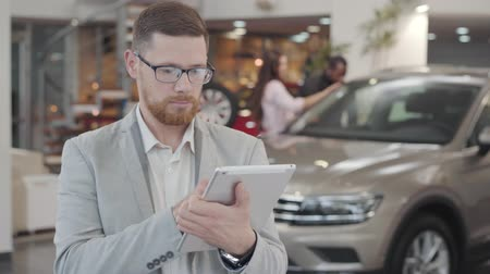 redhead suit : Close-up portrait of serious Caucasian man checking his tablet, looking at camera and gesturing yes by shaking head. Confident successful car dealer at the background of new automobile in showroom.