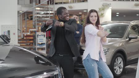 прокат : Happy biracial couple dancing next to the new automobile with car keys. Satisfied African American man and beautiful Caucasian woman bragging their purchase. Car dealership, car business. Стоковые видеозаписи