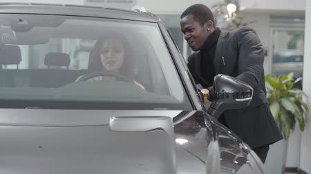 businesslady : Confident African American male dealer talking to young Caucasian woman sitting in car salon. Successful salesman helping client to choose automobile in showroom. Car dealership, car business. Stock Footage