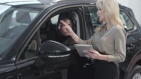 businesslady : Confident blond Caucasian woman with tablet explaining specifications to young African American man sitting in the car salon. Female car dealer selling automobile to rich customer. Car business. Stock Footage