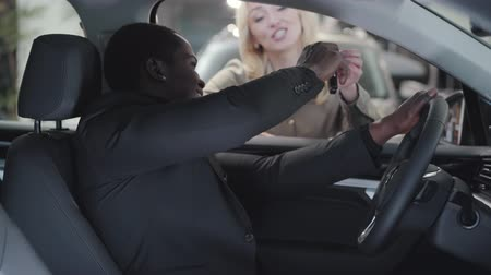 прокат : Blurred Caucasian woman giving car keys to the African American man sitting in salon. Satisfied customer gesturing yes and smiling. Successful female car dealer selling automobile in showroom.