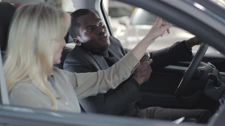 продавщица : Side view of smiling African American man holding car keys and listening to Caucasian car dealer. Blond saleswoman and client sitting in car salon. Trader selling automobile. Car business.