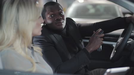 продавщица : Side view of African American businessman sitting in car salon with Caucasian female dealer. Guy holding car keys and listening to vehicle specifications. Blond saleswoman selling automobile. Стоковые видеозаписи