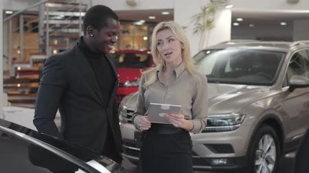 прокат : Confident African American man in black suit talking with female Caucasian car dealer in showroom. Blond woman holding tablet and explaining specifications to customer. Car dealership, car business.