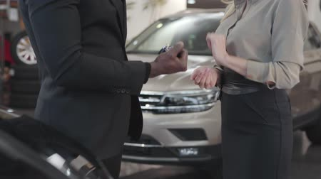 llaves coche : Close-up of female Caucasian hand giving car keys to African American buyer. Happy man gesturing yes. Car dealership, car business. Sale and purchase agreement.