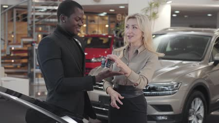 продавщица : Pretty Caucasian woman giving car keys to the African American man in automobile showroom. Happy client gesturing yes and smiling, saleswoman clapping hands. Car dealership, car business.