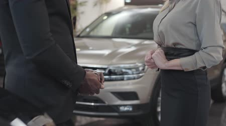 прокат : Close-up of two people shaking hands at the background of new automobiles. Male African American hand taking car keys from Caucasian saleswoman. Car dealership, car business.
