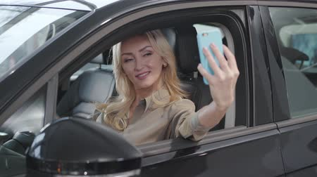 businesslady : Pretty blond Caucasian woman taking selfie in the salon of new car. Successful businesslady taking photos in bought automobile in showroom. Car dealership, car business. Stock Footage