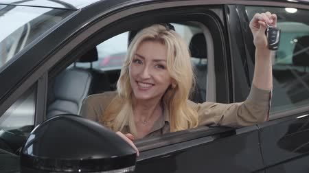 businesslady : Happy Caucasian woman with blond hair sitting in salon and bragging car keys. Successful businesslady buying automobile in showroom. Car dealership, car business. Stock Footage