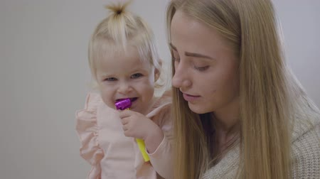 apito : Close-up face of young Caucasian mother with baby girl. Woman talking to her cute little blond daughter, child holding party whistle in mouth. Happy motherhood, family resting together at home. Stock Footage