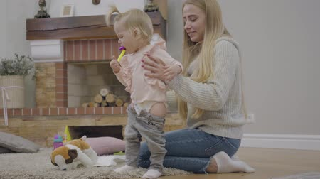 apito : Young Caucasian woman with long hair putting jeans on cute baby girl and taking party whistle off her mouth. Mother dressing her pretty blond daughter. Family preparing for a walk. Happy parenthood. Stock Footage