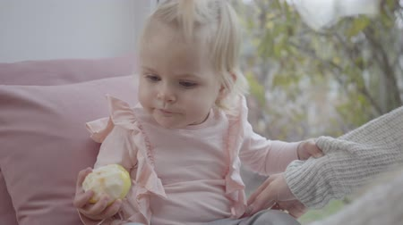blúz : Portrait of little cute Caucasian girl in pink blouse eating an apple. Blond baby child looking around with her beautiful grey eyes and standing up. Mother securing her daughter. Happy parenthood.