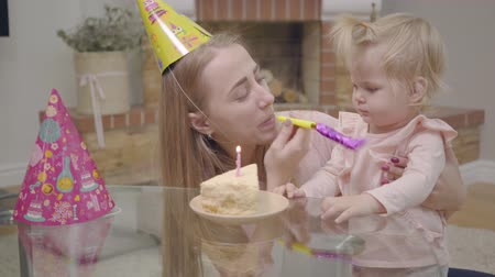 assobio : Young Caucasian mother in party hat and little cute baby girl playing with party whistle. Piece of cake with one candle staying on table in front of them. Child celebrating first birthday with mom.